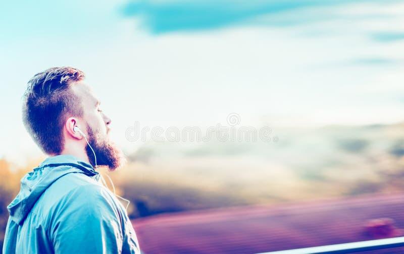 Junger Mann mit einem Bart und einem kurzen Haarschnitt, stehend im Profil gegen unscharfe städtische sonnige Landschaftskopfhöre lizenzfreie stockfotos