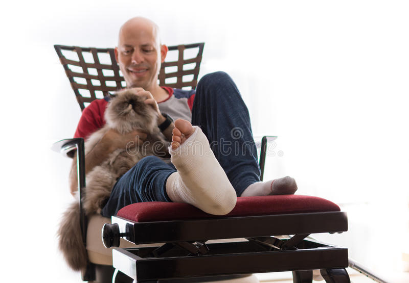 Junger Mann mit einem gebrochenen Knöchel und einer Beinform lizenzfreies stockfoto