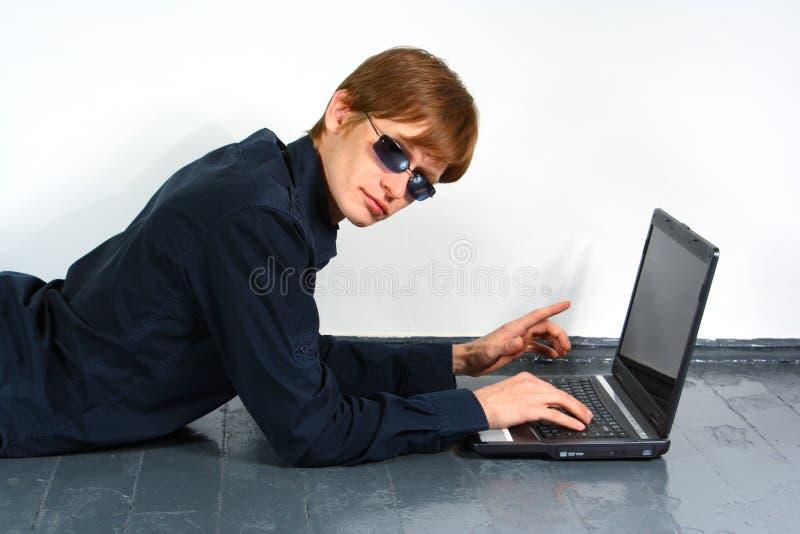 Junger Mann mit einem Laptop stockfotografie