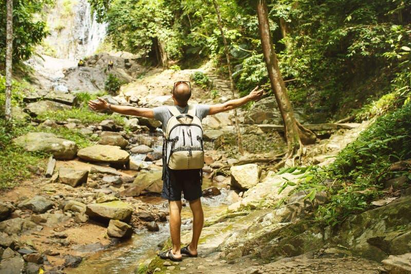 Junger Mann mit einem Reiserucksack nahe einem Wasserfall in Thailand stockfotografie