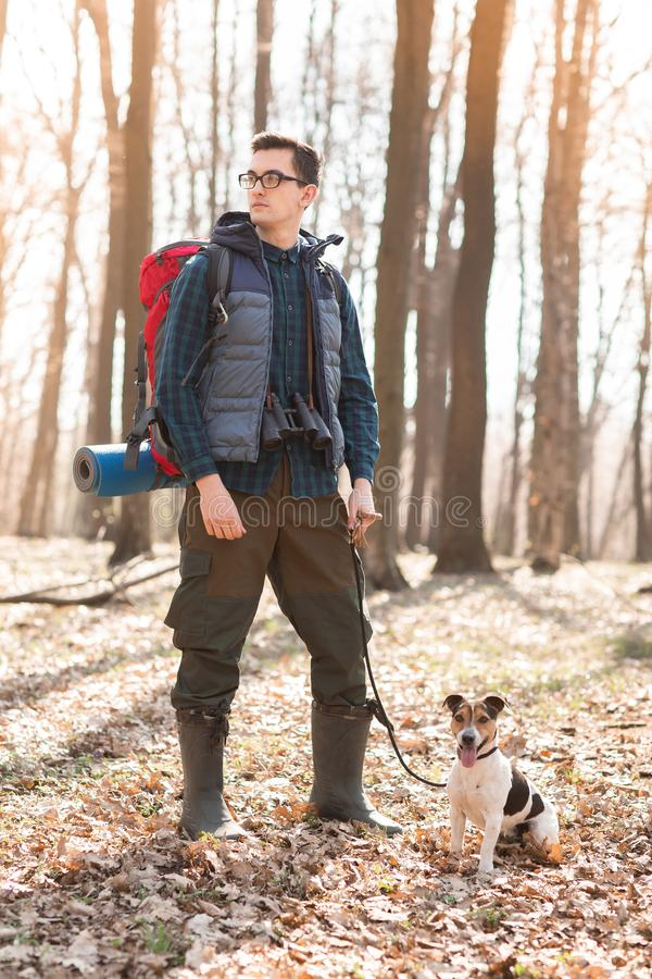 Junger Mann mit einem Rucksack, Ferngläsern und seinem Hund lizenzfreie stockbilder