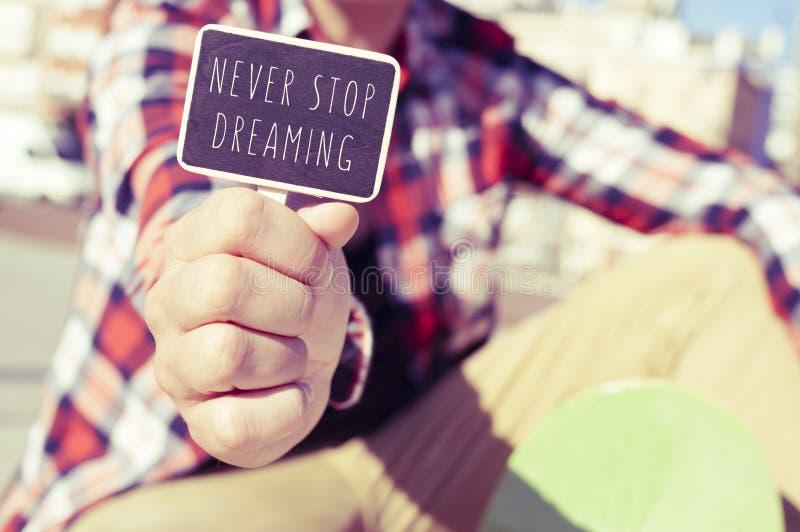 Junger Mann mit einem Schild mit dem Text hören nie auf zu träumen lizenzfreie stockfotografie