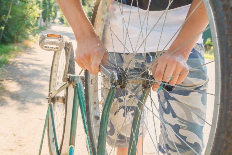junger Mann mit einem Schlüssel repariert ein Rad auf einem alten schmutzigen Fahrrad auf einer Landstraße in den Strahlen stockbild