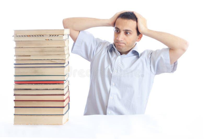 Junger Mann mit einem Stapel der Bücher stockbild