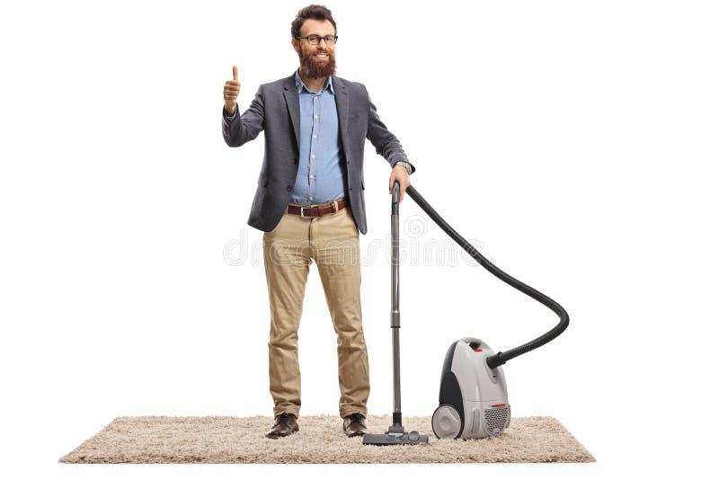 Junger Mann mit einem Staubsauger auf einem Teppich, der sich Daumen zeigt lizenzfreie stockfotos