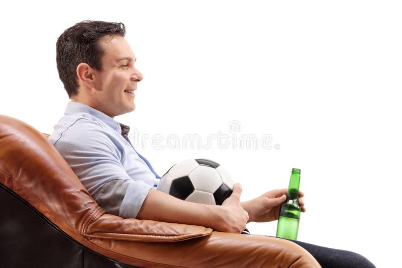 Junger Mann mit einer Bierflasche und einem Fußball, die in einem armcha sitzen lizenzfreies stockfoto