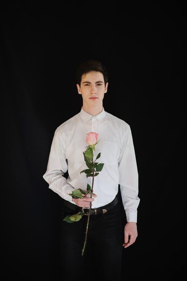 Junger Mann mit einer Rose stockbilder