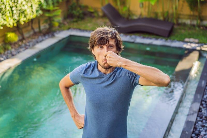 Junger Mann mit Ekel auf seiner Gesichtsklemmnase, etwas stinkt, sehr schlechter Geruch im Swimmingpool wegen des Pools lizenzfreie stockfotografie