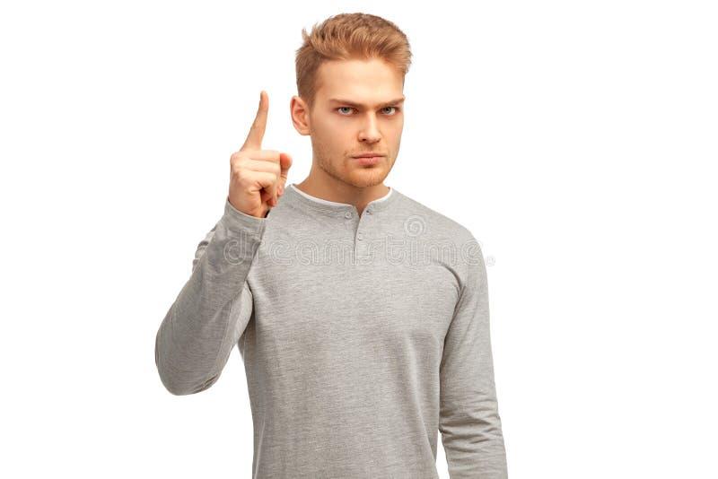 Junger Mann mit ernstem missfallenem Ausdruck, hat Stoppel, helles Haar, Punkte mit dem Zeigefinger aufwärts lizenzfreie stockbilder