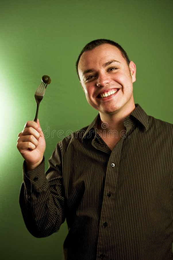 Junger Mann mit Essiggurke auf Gabel lizenzfreie stockfotografie