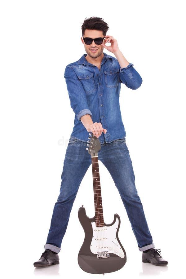 Junger Mann mit Gitarre zwischen Fahrwerkbeinen stockfotografie