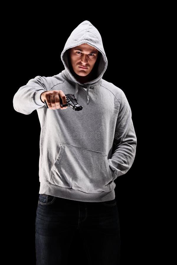 Junger Mann mit Haube über seinem Kopf, der ein Gewehr symbolisiert crim hält stockbilder