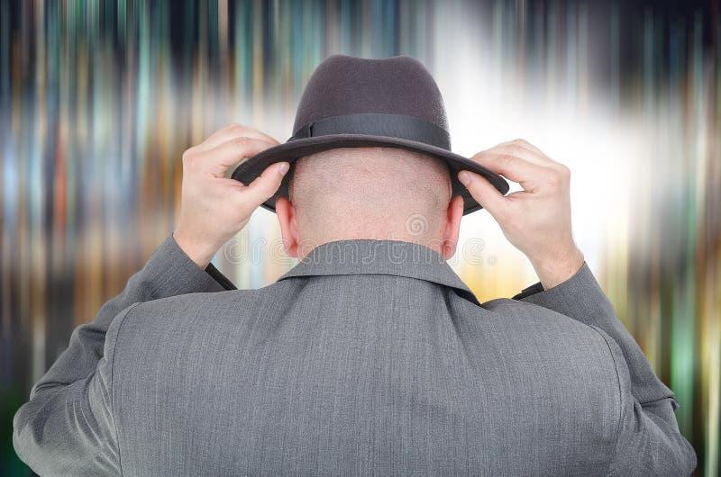 Junger Mann mit Hut von der Rückseite auf farbigem Hintergrund stockfotografie
