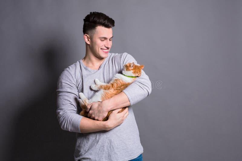 Junger Mann mit Ingwerkatze am grauen Studiohintergrund lizenzfreie stockfotos