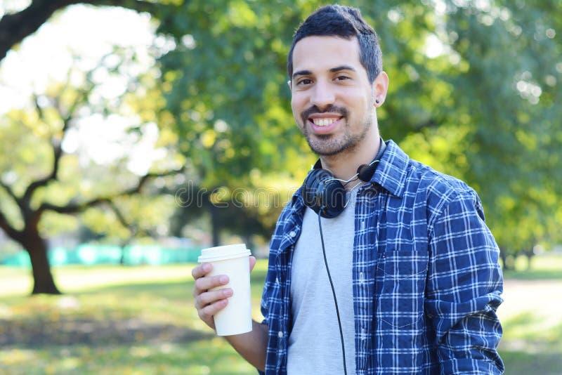 Junger Mann mit Kopfhörern und trinkendem Kaffee in einem Park stockbild