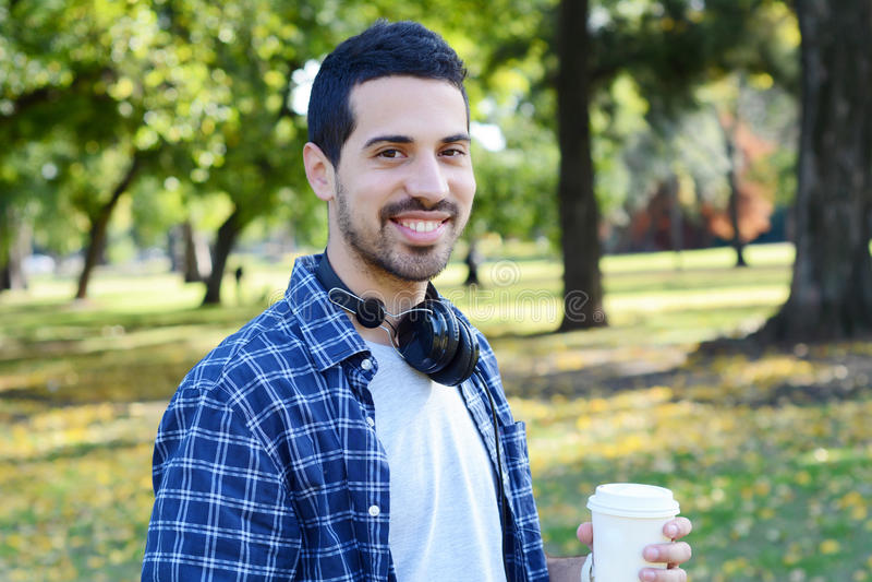 Junger Mann mit Kopfhörern und trinkendem Kaffee in einem Park lizenzfreie stockfotografie