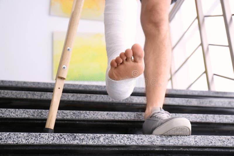 Junger Mann mit Krücke und dem gebrochenen Bein in der Form lizenzfreie stockfotografie