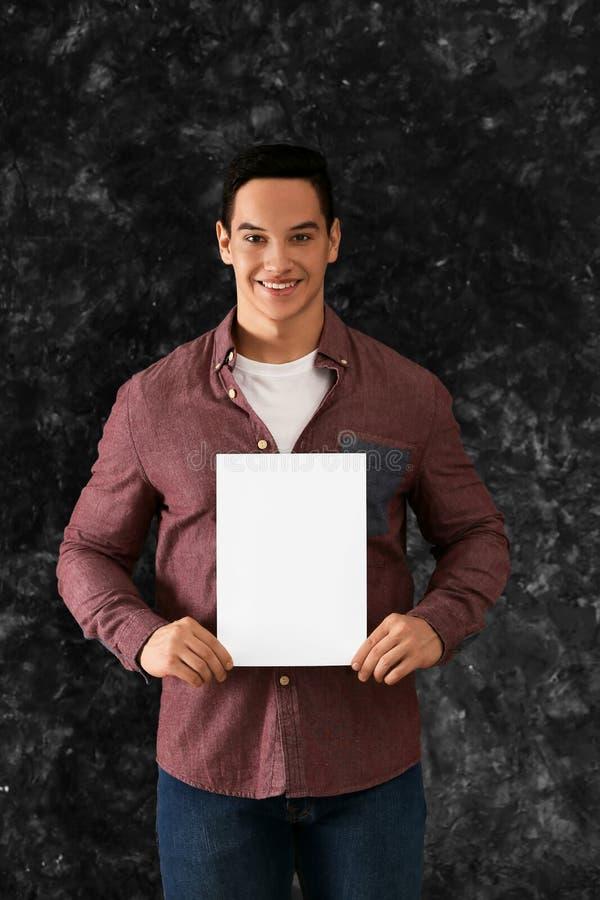 Junger Mann mit leerem Blatt Papier auf grauem Hintergrund lizenzfreie stockfotos