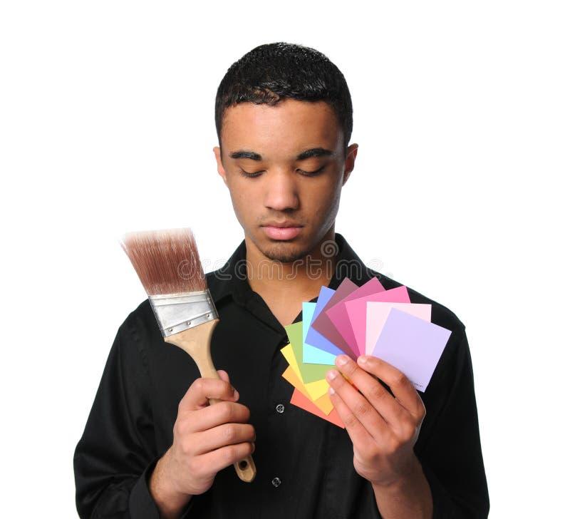 Junger Mann mit Malerpinsel und Mustern stockbild