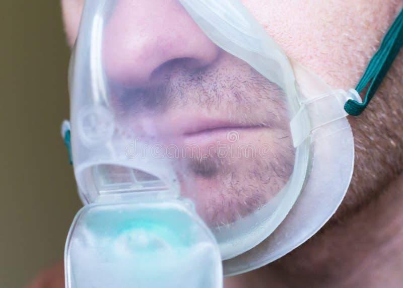 Junger Mann mit Maskensauerstoffeinatmung stockfoto