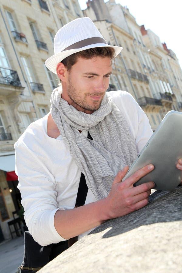 Junger Mann mit modischem Hut unter Verwendung der Tablette draußen stockfoto