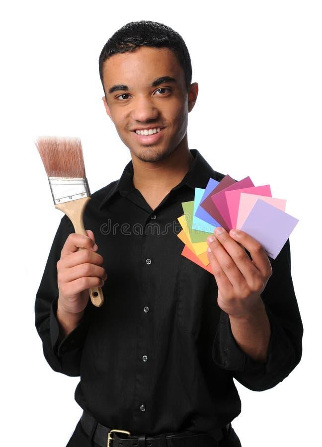 Junger Mann mit Pinsel und Mustern lizenzfreies stockfoto