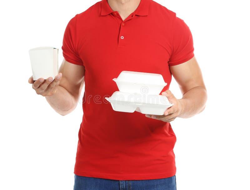 Junger Mann mit Plastikbehältern und Papierkasten auf weißem Hintergrund LebensmittelZustelldienst stockfotos