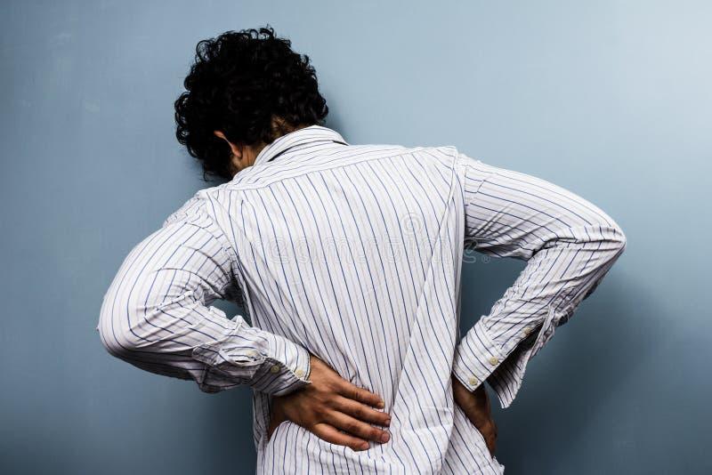 Junger Mann mit Rückenschmerzen stockbild