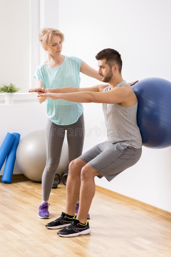 Junger Mann mit Rückenverletzung trainierend mit blauem gymnastischem Ball während der Verabredung mit weiblichem Physiotherapeut stockfotografie