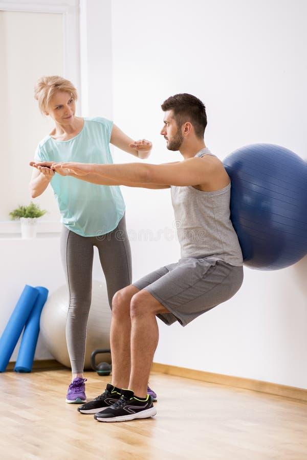 Junger Mann mit Rückenverletzung trainierend mit blauem gymnastischem Ball während der Verabredung mit weiblichem Physiotherapeut stockbild