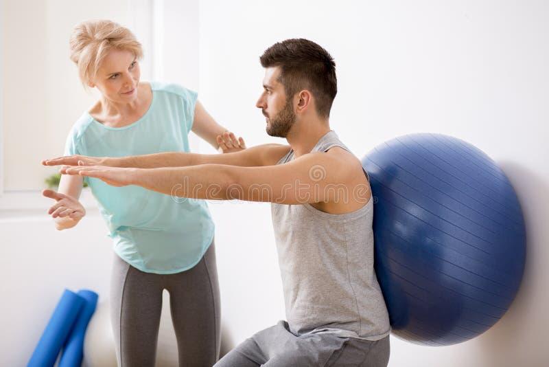 Junger Mann mit Rückenverletzung trainierend mit blauem gymnastischem Ball während der Verabredung mit weiblichem Physiotherapeut lizenzfreie stockfotos
