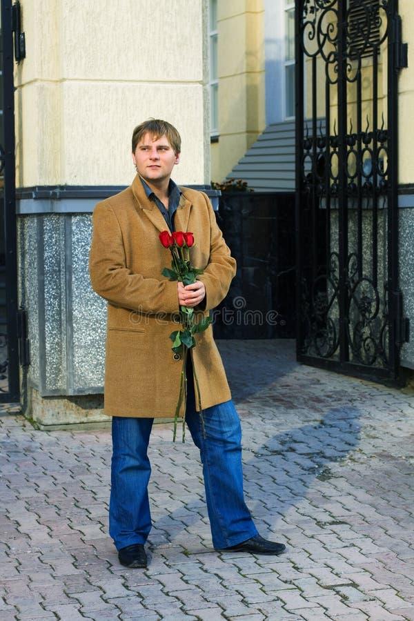 Junger Mann mit Rosen. stockbilder