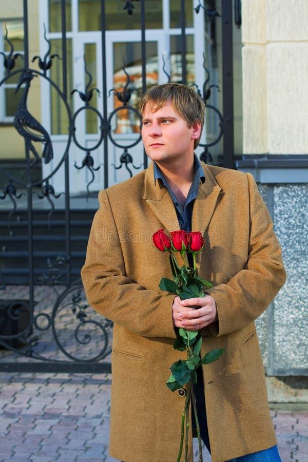 Junger Mann mit Rosen. stockfotos