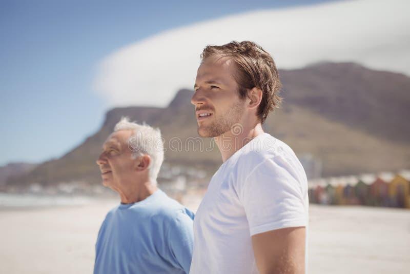 Junger Mann mit seinem Vater, der am Strand steht stockfotos
