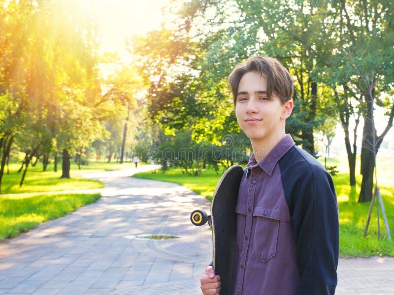 Junger Mann mit Skateboard im Stadtpark Jugendlich Jungenschlittschuhläufer lizenzfreie stockbilder