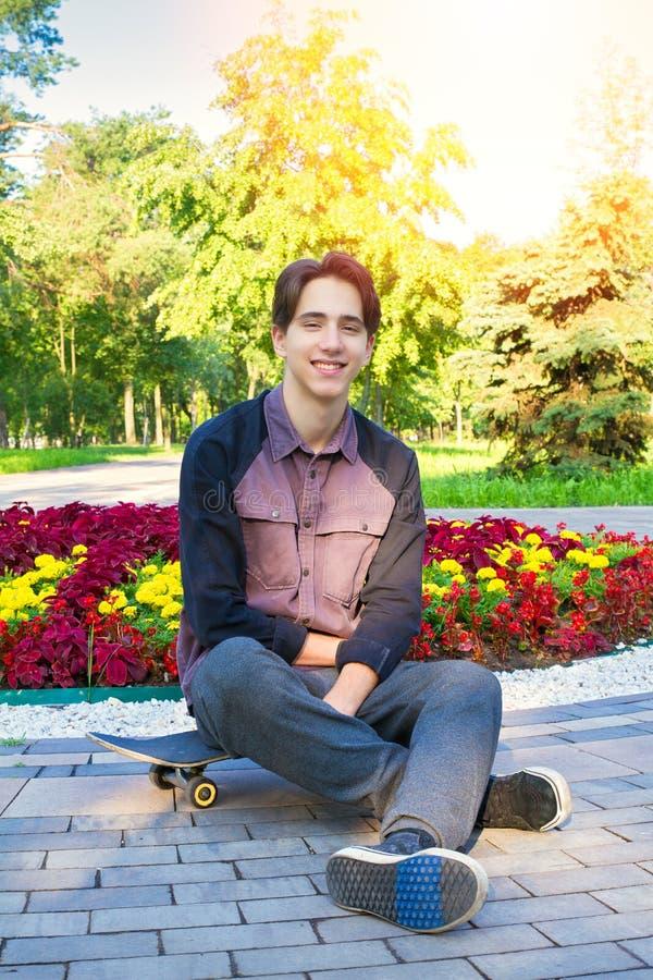 Junger Mann mit Skateboard im Stadtpark Jugendlich Jungenschlittschuhläufer lizenzfreie stockfotografie