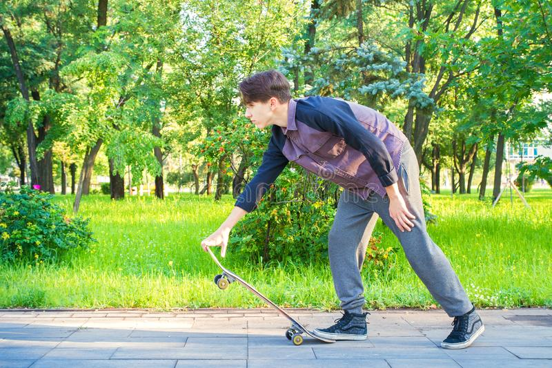 Junger Mann mit Skateboard im Stadtpark Jugendlich Jungenschlittschuhläufer lizenzfreies stockbild