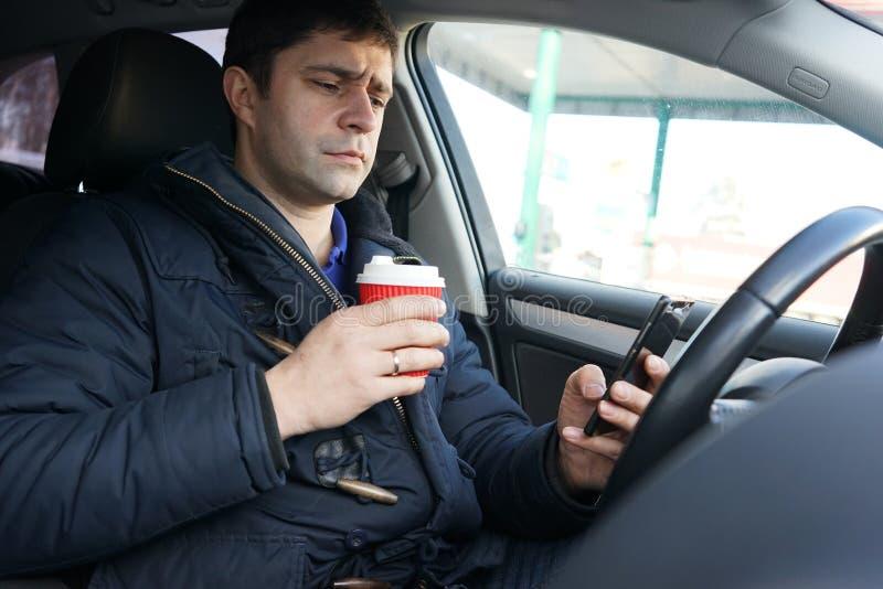Junger Mann mit Smartphone und Kaffee im Auto lizenzfreie stockfotos