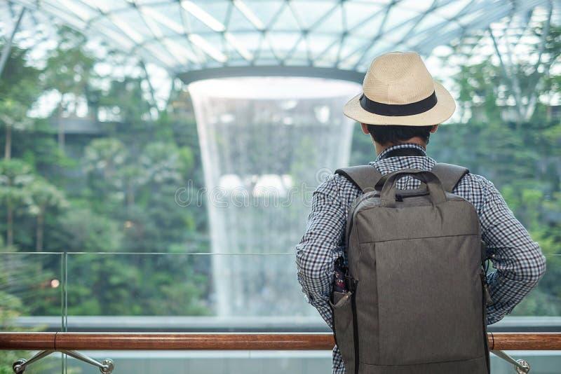 Junger Mann mit Tasche und Hut, asiatische Reisendstellung und Betrachten zur schönen Regenturbulenz Juwel Changi-Flughafen, Mark lizenzfreie stockfotografie