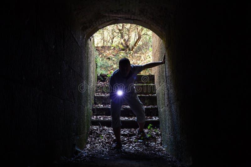 Junger Mann mit Taschenlampe betritt den Steintunnel stockfotografie