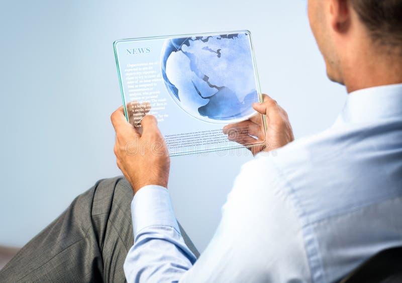 Junger Mann mit transparenter futuristischer Tablette lizenzfreies stockbild
