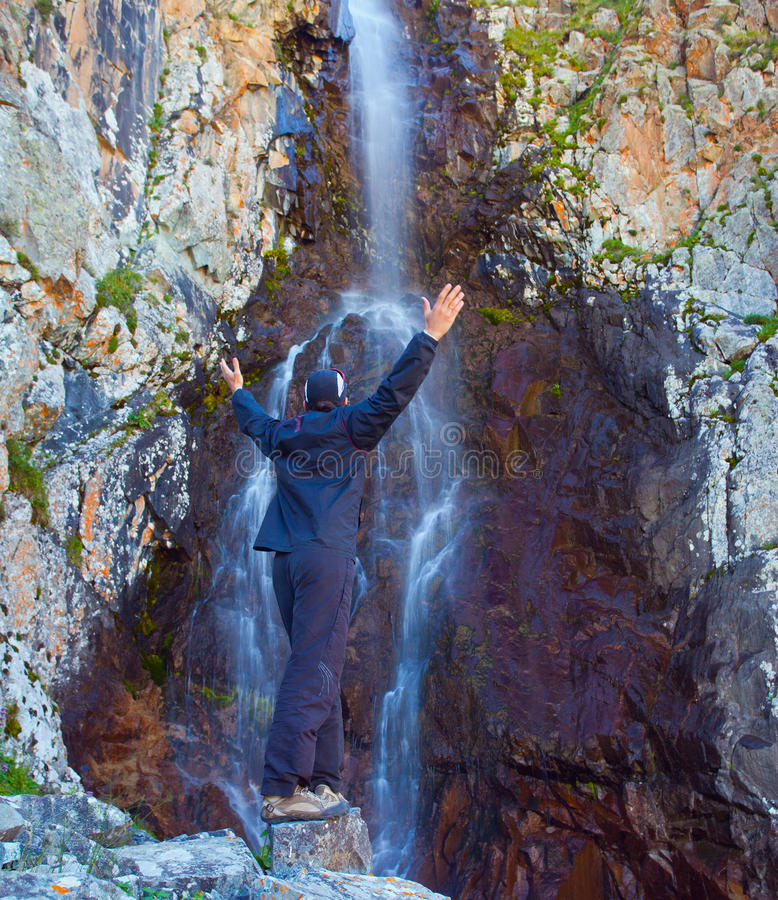 Junger Mann nahe Wasserfall in den Bergen, Ala-Archa, Kirgisistan stockfoto