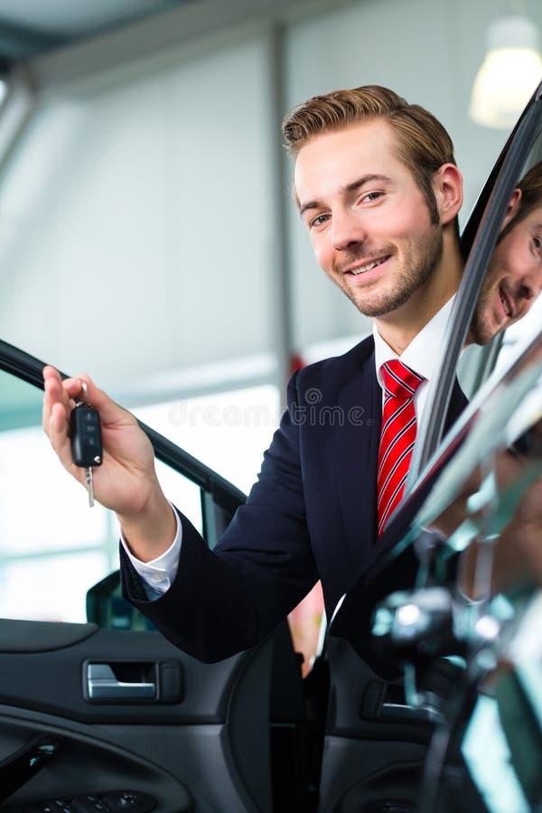 Junger Mann oder Autohändler im Auto-Vertragshändler stockbilder