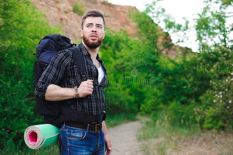 Junger Mann-Reisender mit der Rucksackentspannung im Freien Sommerferien und Lebensstil Konzept wandernd lizenzfreie stockbilder