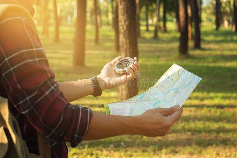 Junger Mann-Reisender mit Rucksack, Betrachtenkarte und Kompass relaxi stockfotografie