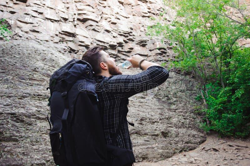 Junger Mann-Reisender mit Trinkwasser des Rucksacks und Entspannung im Freien lizenzfreie stockfotografie