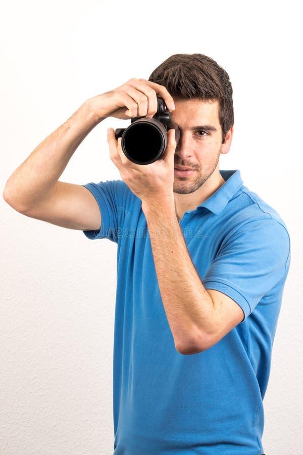 Junger Mann schaut durch eine Kamera stockfotografie