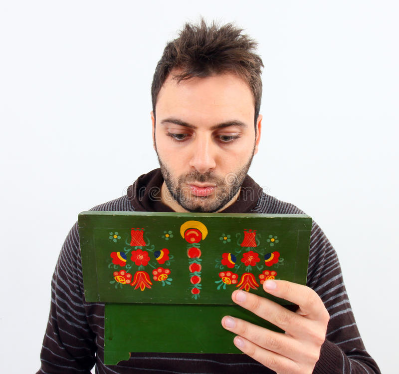 Junger Mann schaut innerhalb einer Holzkiste stockfoto