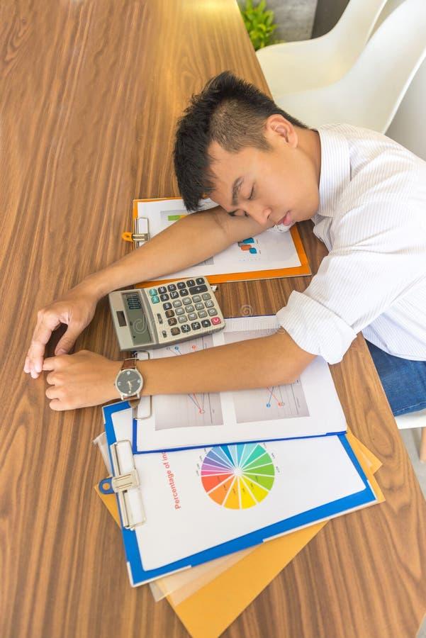 Junger Mann schlafen auf Arbeitsschreibtisch mit Finanzdokumenten ein stockfotos