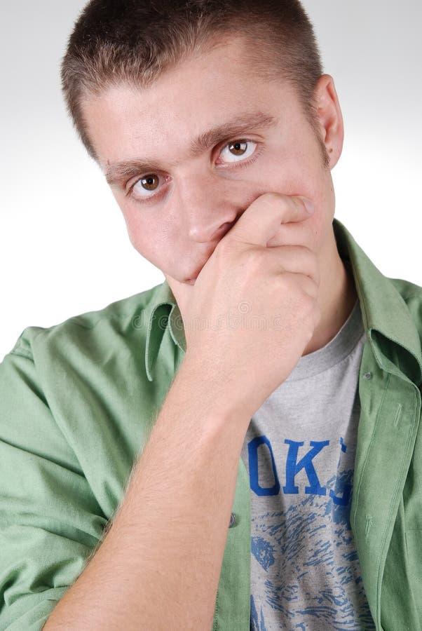 Junger Mann, seinen Mund mit der Hand kleidend lizenzfreie stockbilder